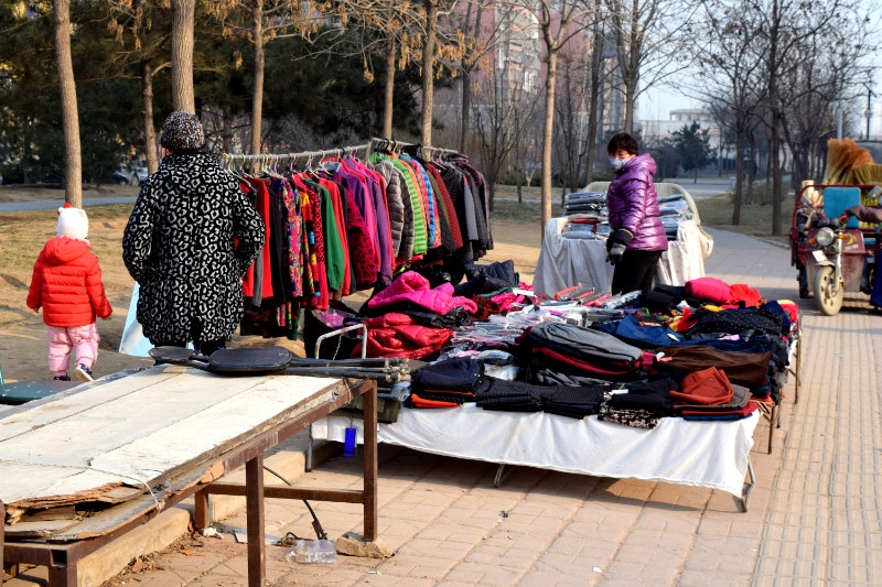 A small stall of clothes on the side of the street in beijing