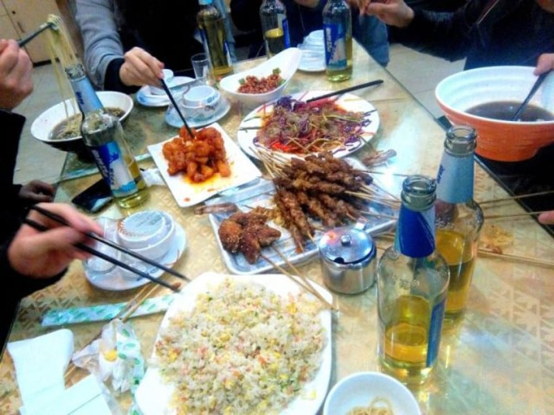 A large buffet of chinese food with people sat around eating