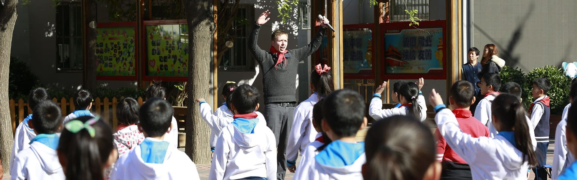 A man in front of many chinese children playing games