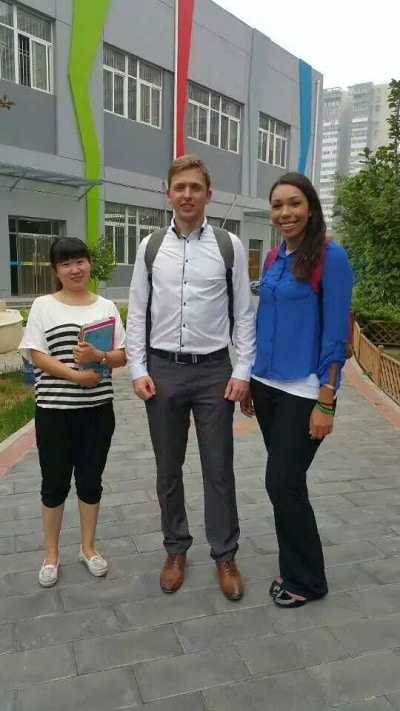 Two tall people with a small chinese teacher