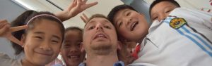A teacher being swamped by chinese children who want to be in the photo