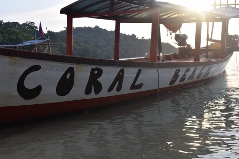 A boat in the sea with coral beach on the side of it