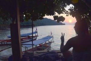 A lady making a peace sign with a sunset into the bay in the background