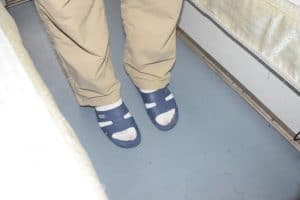 Woman's legs in brown trousers wearing blue plastic slippers and white socks