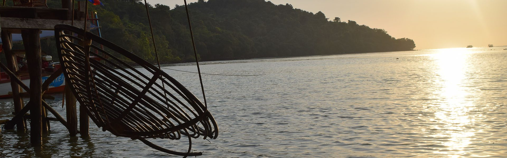 A wooden basket swing over the water in a sunset on koh ta kiev island