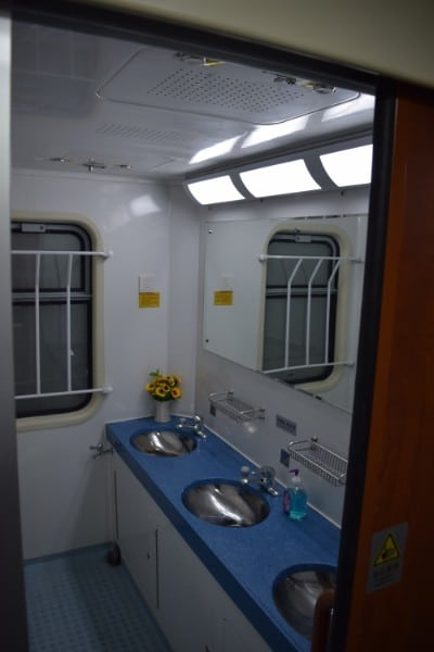 Blue counters with 2 sinks and a large mirror in front