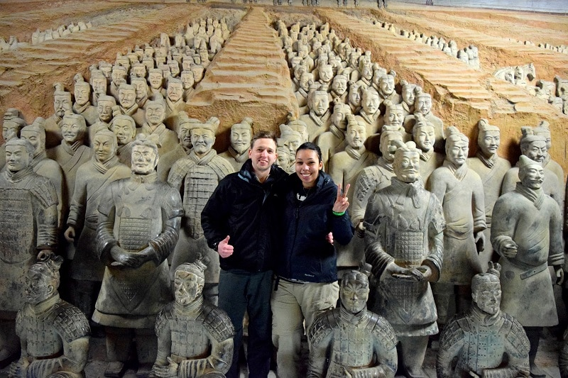Two people with a collection of terracotta warriors