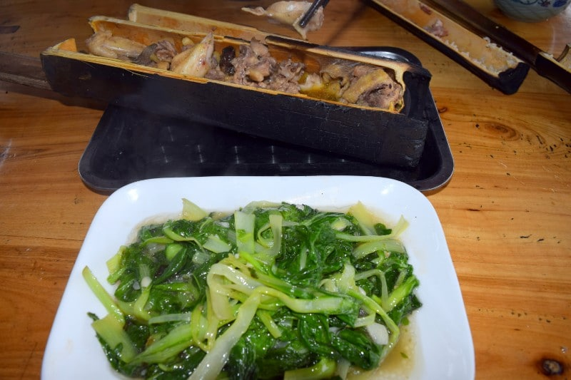 Green steaming vegetables and rice in piece of bamboo