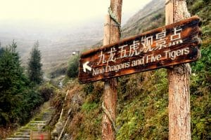 Signpost for Nine Dragons and Five Tigers pointing up some stairs with misty mountains in the background
