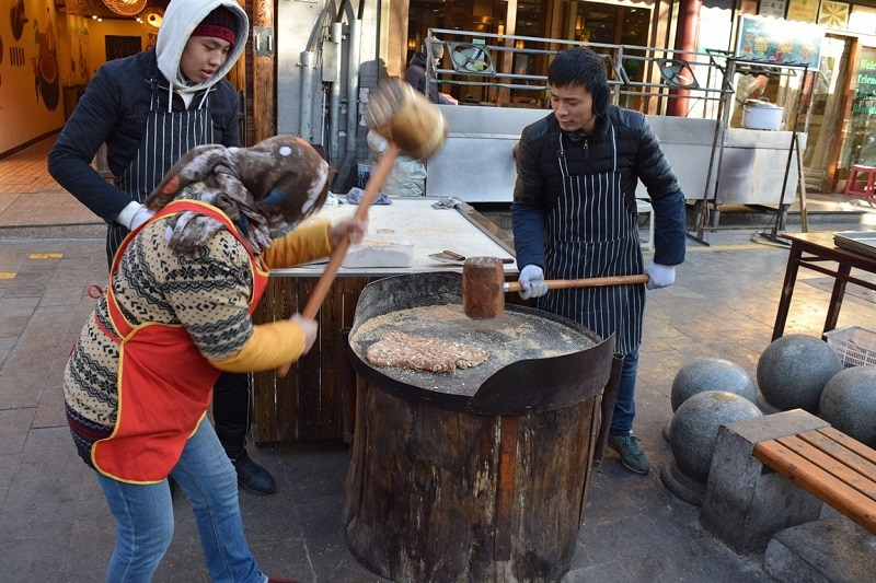 2 People with large mallets hammering dough