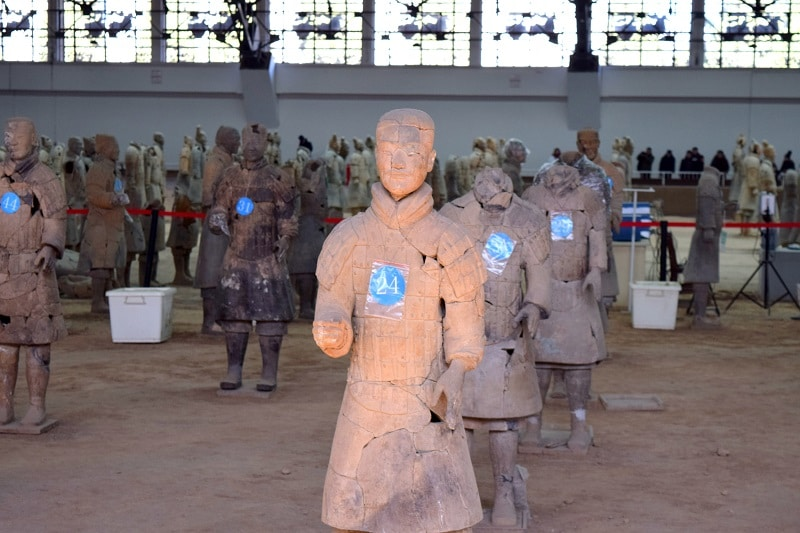 A line of terracotta warriors being repaired and rebuilt
