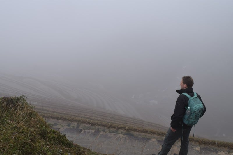 Man standing on the edge of the rice terraces with thick fog
