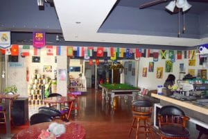 Bar with multi coloured flags hanging from the door frame and a pool table