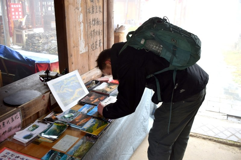 Man wearing a green rucksack bending down to write a postcard