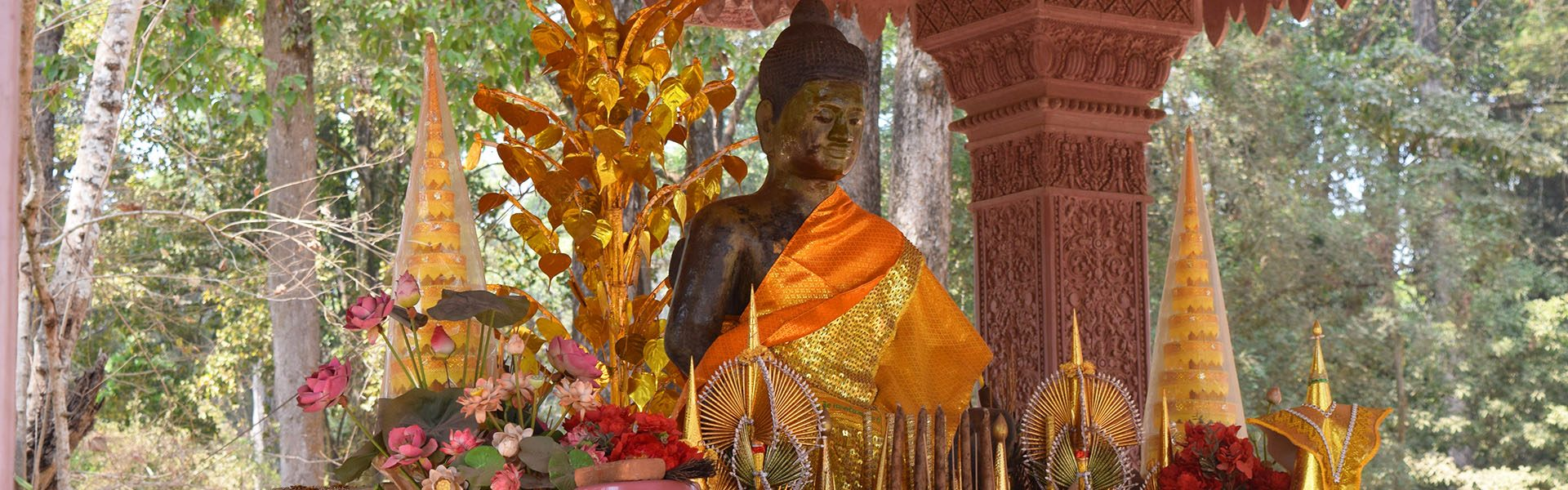 A golden Statue surrounded by brightly covered trinkets