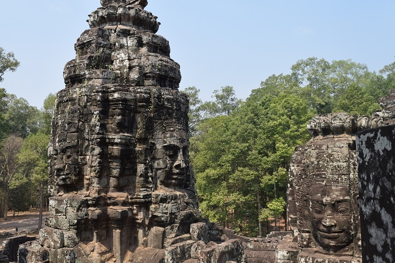 Angkor Wat ruins with large preserved faces staring out of the walls