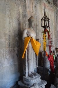 A statue at Angkor Wat holding some orange linen