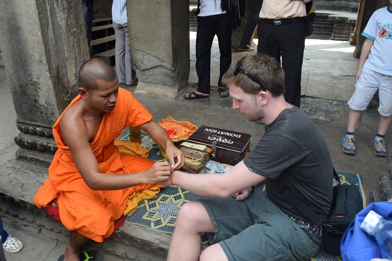 A man getting a red band tied to his wrist by a monk