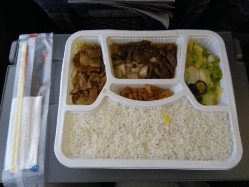 A pair of chopsticks next to a white tray with 5 compartments of food including rice and vegetables