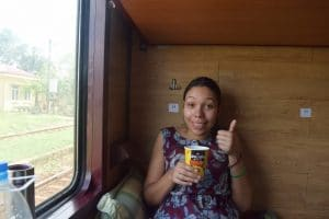 A woman sitting on a train holding a pot of instant noodles with her thumb up