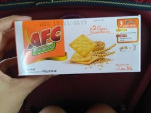 A hand holding a box of cracker with orange and white packaging