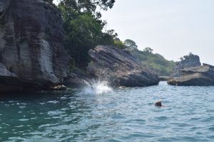 A view from the boat of people jumping in the water from a big rock