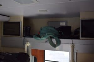 A green rucksack in the storage area above the open door of a train compartment