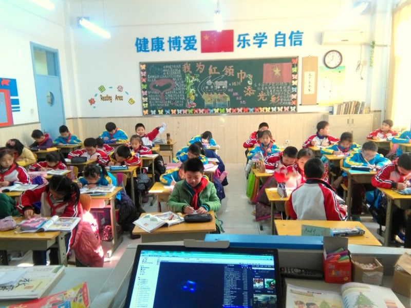 A group of chinese students colouring in christmas trees in class
