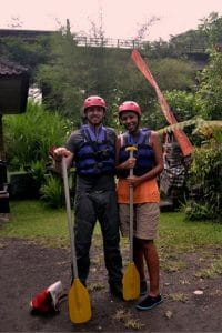 Two people holding paddles posing before going white water rafting in bali
