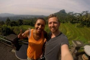 2 people in front of a large hill with rice terraces running down the side