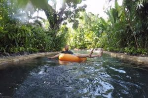 A man floating on an orange ring on a lazy river