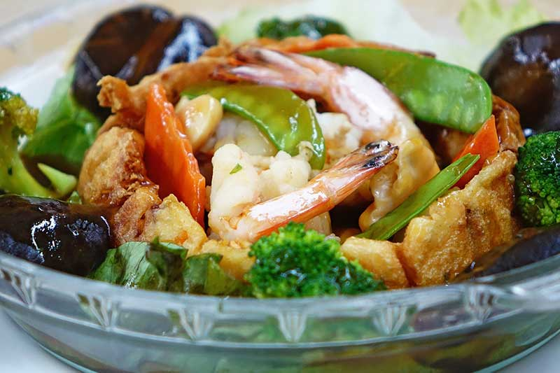 Chinese food in a bowel with prawns and veg.