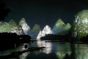 A bay in the Li river in china surrounded by hills that are lit up. Best things to do in Guilin