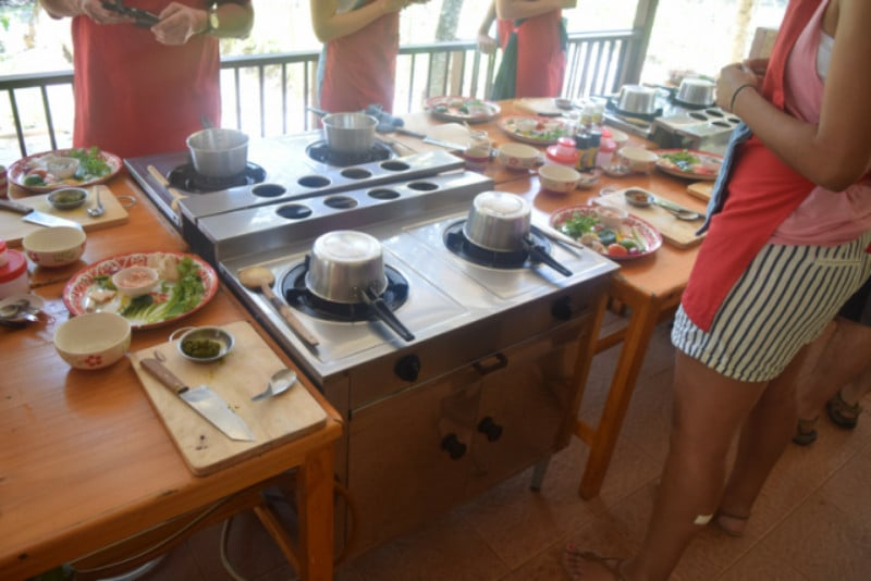 A long table full of pots and pand and ingredients for a chiang mai cooking school