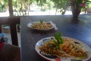 Two Pad Thai dishes on a dark wooden table in chiang mai