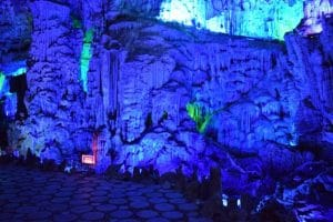 Blue lit cave with stalagmites and stalactites