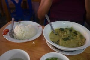 A thai green curry with a bowl of steamed rice in thailand