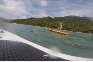 A woman falling off of a paddle board into the thai sea