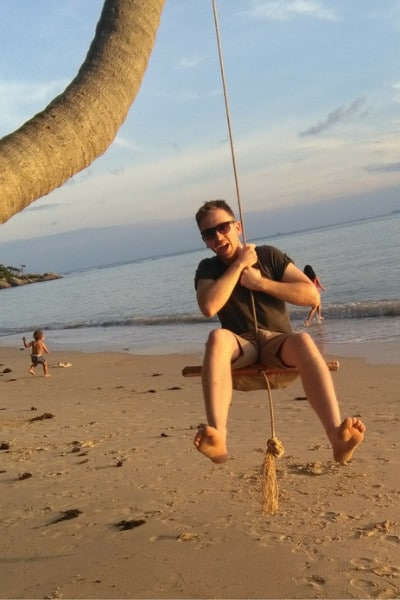 A man swinging from a rope swing next to the sea looking very happy