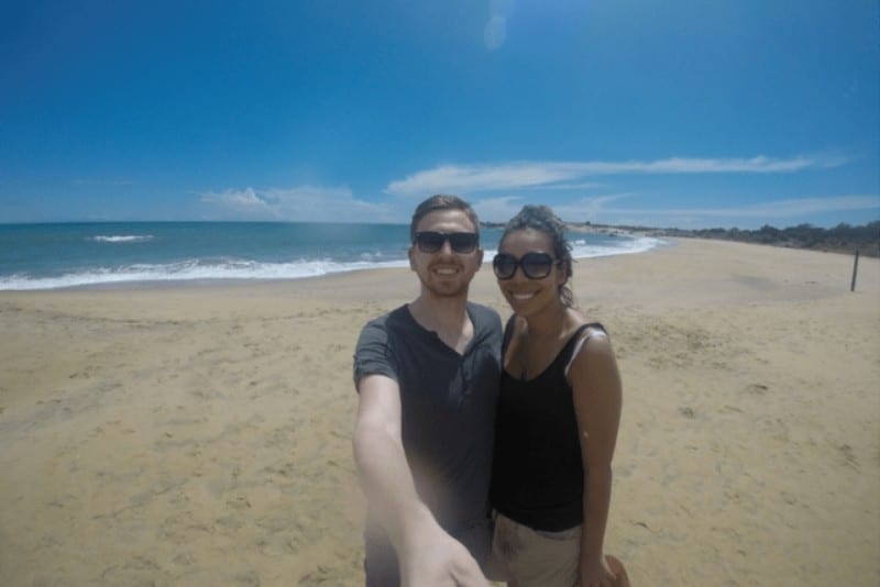 A woman and a man taking a selfie on a beach with the sea in the background