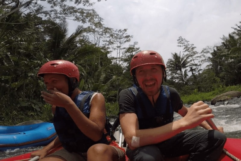 A woman and a man wearing red helmets laughing on a raft during white water rafting