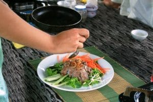 A hand hovering over a finished meal at an asian cooking class