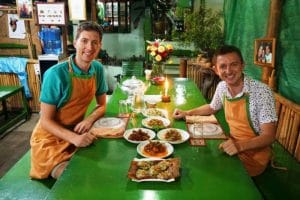2 men sat at a table in aprons with food they prepared