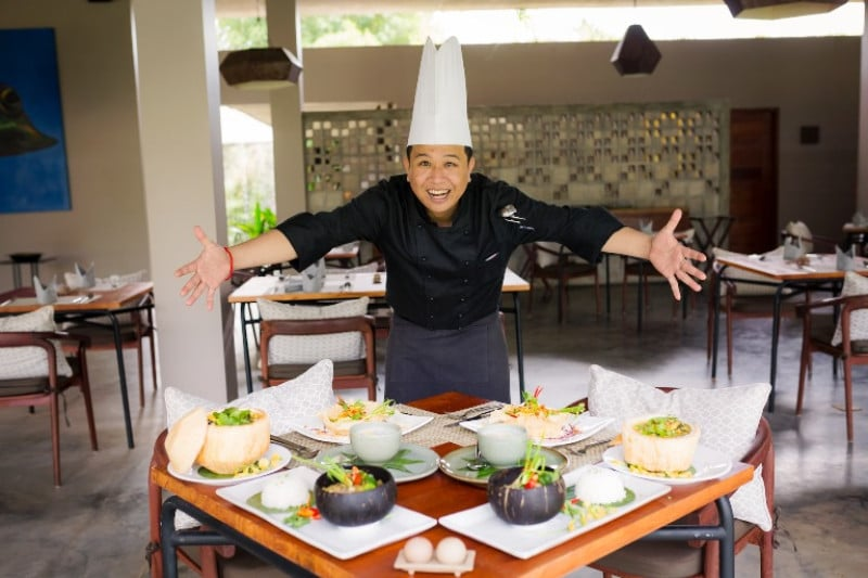 A chef leaning over his food happily
