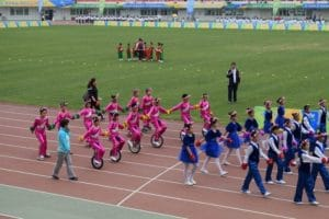 A group of children in a stadium on parade in China
