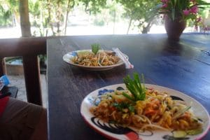 2 plates of pad thai on a dark wood table
