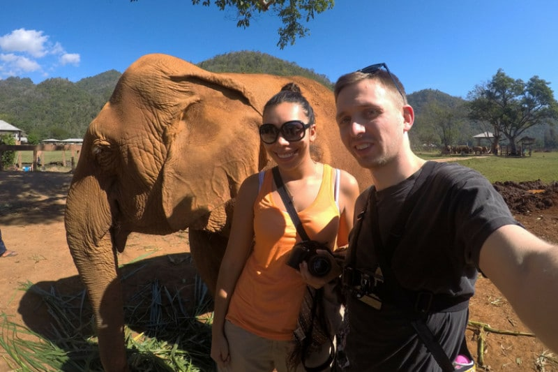 2 people with an elephant in the background