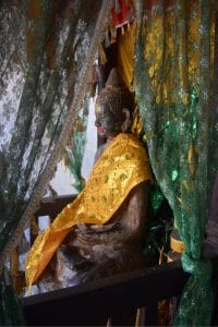 A statue in ankor wat with golden cloth over it