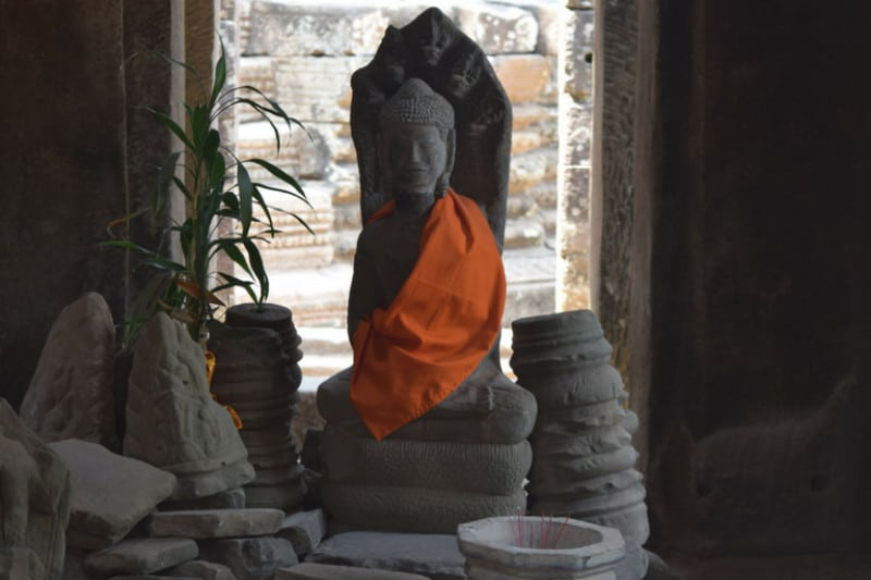 A cambodian statue with an orange cloth over its shoulder