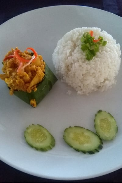 A curry and rice dish in cambodia with the curry wrapped in a bamboo leaf